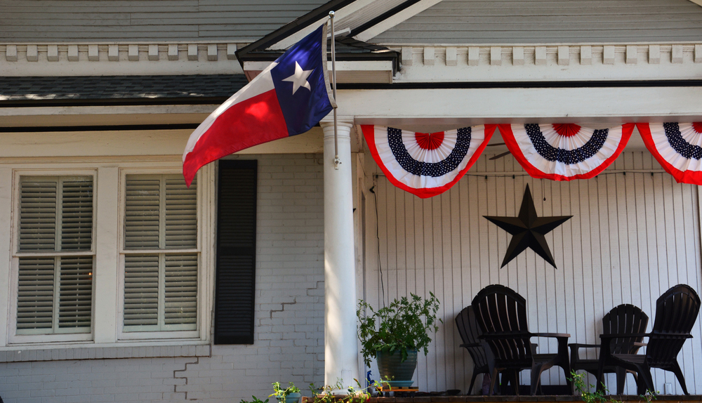 Front porch of a home flying the Texas state flag