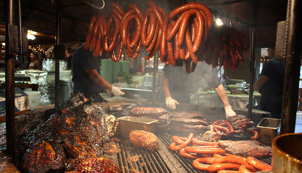 Sausages and various cuts of barbecued meat being grilled