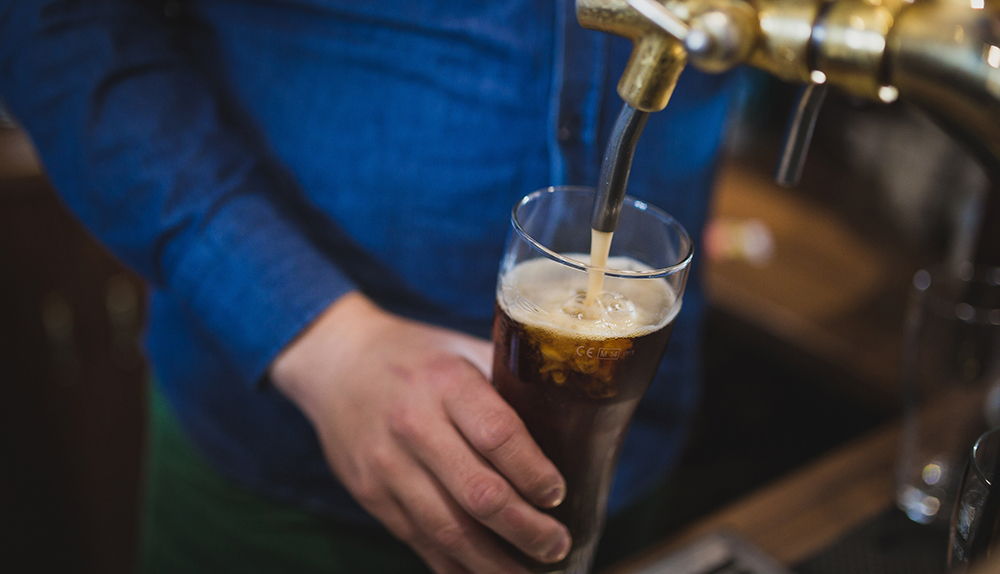 A man pouring beer into a pint glass.
