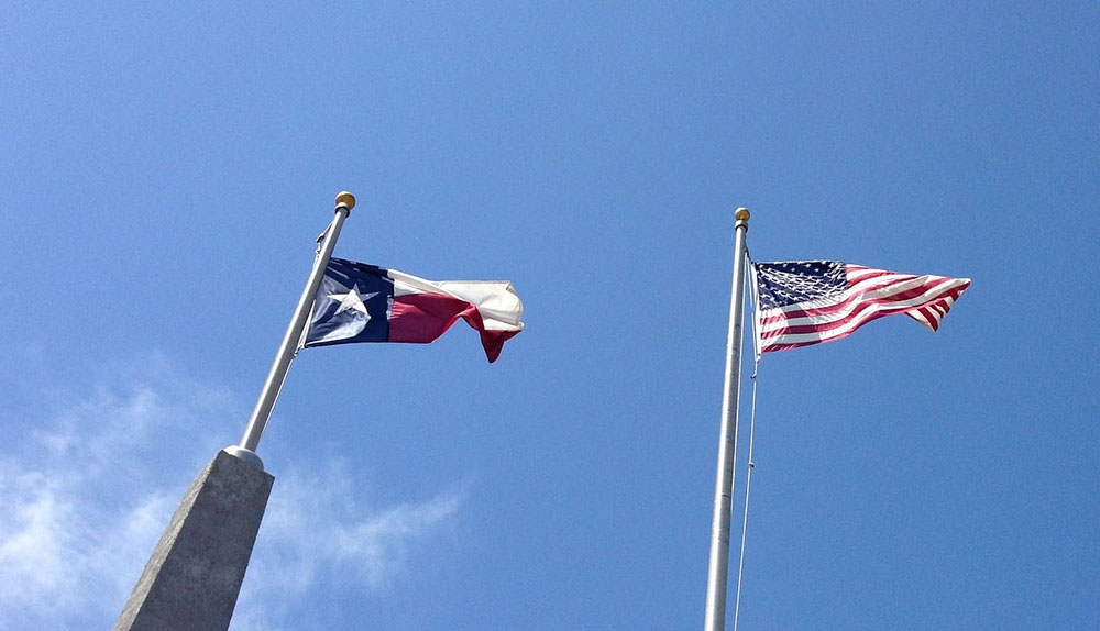 Texas State Flag and American flag flying side by side.