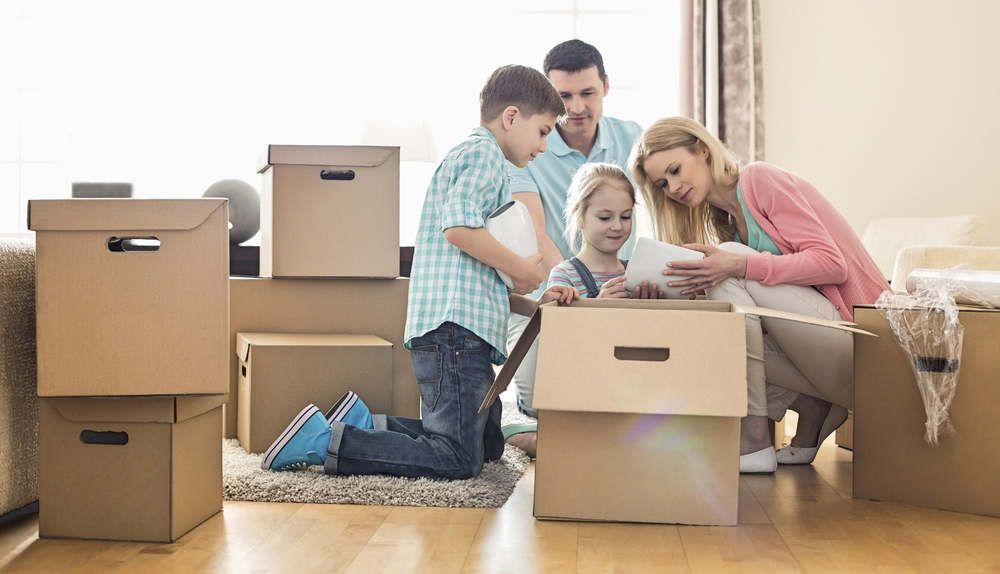 Parents and two young children unpacking boxes