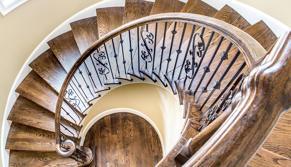 An overhead photograph looking down an ornate, circular stairwell in a luxury home