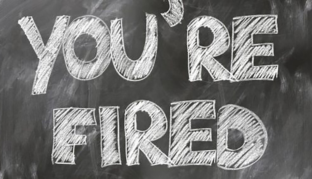 An image of a chalkboard with the words You're Fired written on it.