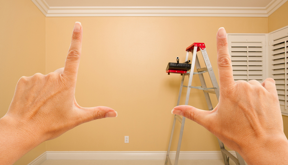 A woman's hands making a frame before a wall with a ladder and paint brushes in the background