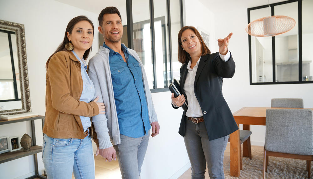A young couple being shown a home by a Realtor