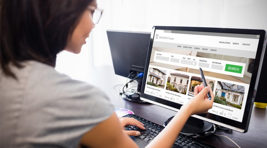 A woman looking at homes for sale on a computer