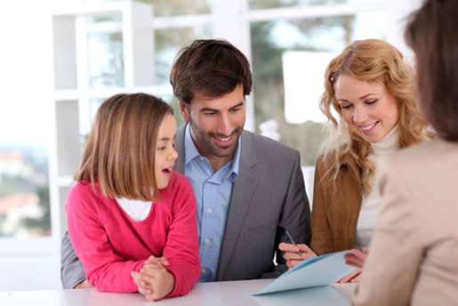 A family signs documents in front of a Realtor