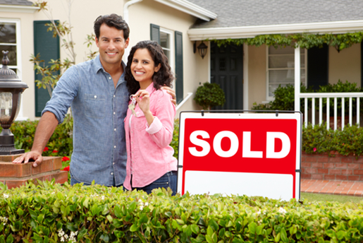 A couple stands next to a sold sign in front of a house
