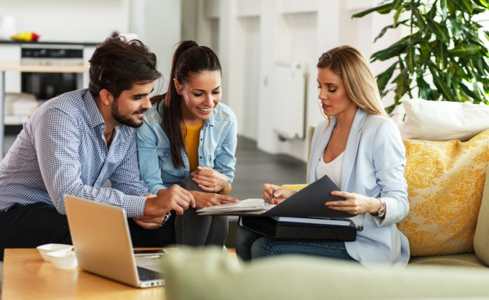 Young couple and Realtor looking at documents