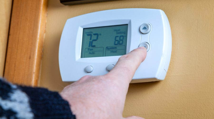 A person adjusting the temperature on a home thermostat