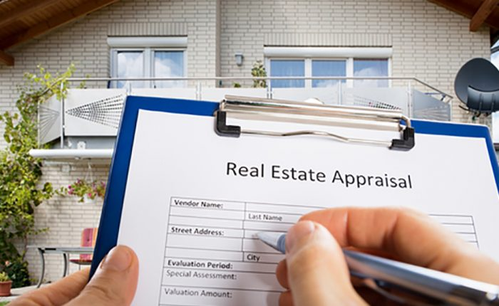 Image of an individual signing a real estate appraisal form