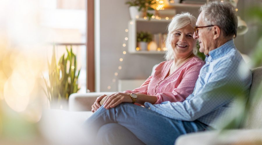 A senior citizen couple sitting on a couch in their living room
