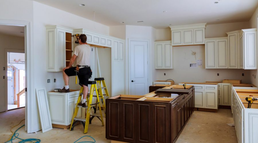 Kitchen cabinets being installed during a restoration project